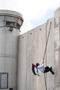 Palestinian climbs Israeli separation wall Stock Photography