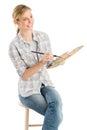 Paleta femenina de with paintbrush and del artista que se sienta en taburete Fotografía de archivo libre de regalías