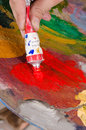 Palette of colors painter squeezing red paint onto his Stock Image