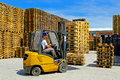 Pallet forklift operator handling wooden pallets in warehouse Royalty Free Stock Image