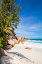 Palms at the beach tropical with green and brown granite rocks a turquoise sea and a blue sky with white clouds seychelles la Royalty Free Stock Photo