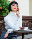 Pamper yourself. Girl relax cafe with cake dessert. Woman attractive elegant brunette eat gourmet cake cafe terrace Royalty Free Stock Photo