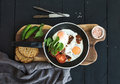 Pan of fried eggs, bacon, tomatoes with bread, mangold and cucumbers on rustic wooden serving board over dark table Royalty Free Stock Photo