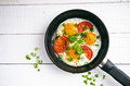 Pan of fried eggs with tomatoes, cheese, spring onion, herbs on a white table. White wooden table. Concept of food. Breakfast time Royalty Free Stock Photo
