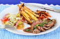 Pan grilled flank steak soy mustard sauce plate butter roasted carrots roasted potatoes vegetable salad olive oil vinegar Stock Photo