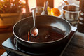 Pan with liquid and spoon cinnamon stick dark wine sauce cinnamon sweet aroma taste Royalty Free Stock Photo