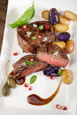 Pan seared steak with fingerling potatoes capers pomegranate balsamic vinegar sauce and fresh basil Royalty Free Stock Photography