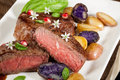 Pan seared steak with fingerling potatoes capers pomegranate balsamic vinegar sauce and fresh basil Royalty Free Stock Images