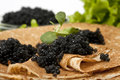 Pancake with black caviar Royalty Free Stock Images