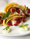 Pancake filled with strawsberries and garnished with mint syrop and whipped cream fresh fried golden Stock Photo