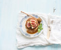 Pancake tower with fresh figs and honey on a rustic plate. Light blue  background Royalty Free Stock Photo