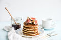 Pancake tower with fresh figs and honey on a rustic plate. White background Royalty Free Stock Photo
