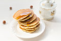 Pancakes with berries and maple syrup stack of summer drizzled honey on white plate on white table Royalty Free Stock Photos