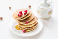 Pancakes with berries and maple syrup stack of summer drizzled honey on white plate on white table Royalty Free Stock Images