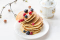 Pancakes with berries and maple syrup stack of summer drizzled honey on white plate on white table Stock Photography