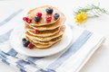 Pancakes with berries and maple syrup stack of summer drizzled honey on white plate on white table Stock Images