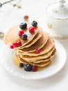 Pancakes with berries and maple syrup stack of summer drizzled honey on white plate on white table Stock Photo