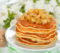 Pancakes with caramelized apples on a white table Royalty Free Stock Photos