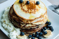 Pancakes with honey and cream fruit on a white plate Royalty Free Stock Photo
