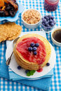 Pancakes with jam breakfast food and blueberries black coffee cereal and dried fruit Royalty Free Stock Images