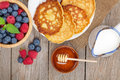 Pancakes with raspberry, blueberry, milk and honey syrup Royalty Free Stock Photo