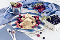 Pancakes with raspberry, currant on blue stripped plate with textile, close-up white marble background Royalty Free Stock Photo