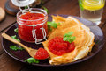 Pancakes with red caviar on plate