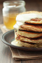 Pancakes stack of with condensed milk on wooden background Stock Image