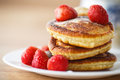 Pancakes with strawberries and powdered sugar on a plate Stock Images