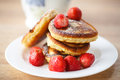 Pancakes with strawberries and powdered sugar on a plate Royalty Free Stock Images