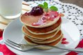 Pancakes on a white plate with strawberry jam Stock Photo