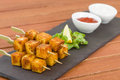 Paneer tikka kebab tandoori indian cheese skewers served on a slate with lemon chili sauce and cucumber and red onion yoghurt Stock Photo