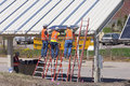 Panel installation on solar carport may workers at great river energy headquarters install panels for powered carports in maple Stock Photo
