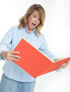 Panicked woman examining a book in business casual clothes Stock Photo