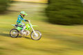 Panning motion blur of boy riding green dirt bike Royalty Free Stock Photo