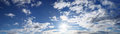 Panorama of blue sky with sun and clouds Royalty Free Stock Photo