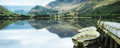 Panorama landscape rowing boats on lake with jetty against mount mountain range background Royalty Free Stock Photos