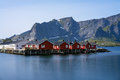 Panorama of mount Olstind above the red fishing houses called Rorbu in town of Hamnoy on Lofoten islands, Norway Royalty Free Stock Photo
