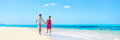 Panorama summer vacation couple walking on beach young adults having fun together enjoying their holidays travel in perfect Royalty Free Stock Photo