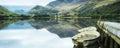 Panoramalandschap het roeien boten op meer met pier tegen onderstel Royalty-vrije Stock Foto's