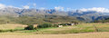 Panoramic farm landscape with high mountains and fields Royalty Free Stock Photo