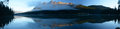 Panoramic image of lucerne peak lit by the rising sun reflected in calm waters yellowhead lake on early summer morning lake is Royalty Free Stock Photography
