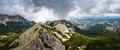 Panoramic landscape of mountain ridge and cloudy gray dramatic sky in the summer.