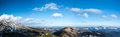 Panoramic scenery of mountains and valleys under blue sky with scattered clouds Stock Images