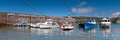 Panoramic shot of small boats in a harbour panorama fishing and pleasure craft the at port erin the isle man on summer day with Royalty Free Stock Image