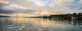 Panoramic summer view of boat cruise excursion landscape on Zurichsee with beautiful sunset shining light through clouds reflected Royalty Free Stock Photo