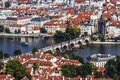 Panoramic view from above of Prague, Charles bridge with crowds of tourists, the Vltava river and red roofs.