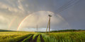 Panoramic view of beautiful Russian landscape. Double rainbow over green wheat fields and power lines Royalty Free Stock Photo