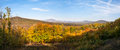 Panoramic view of colorfull forest beautiful autumn panorama with distant hills and castle ruin Royalty Free Stock Photography