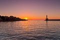 Panoramic view of the entrance to Chania harbor with lighthouse at sunset, Crete Stock Image